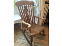 A LOVELY VINTAGE SOLID OAK ROCKING CHAIR WITH CLASSIC DESIGN TO THE BACK AND LOVELY GRAIN TO THESEAT