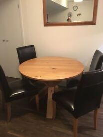 Next round light wood table and 4 black high back chairs in excellent condition