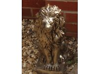 A pair of solid bronze effect sitting lions