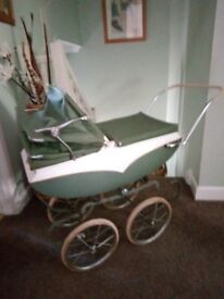 1950'S Triang doll's pram in green and white with hood and pram cover.