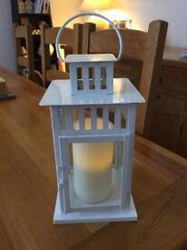 Large white metal lantern with separate LED pillar candle
