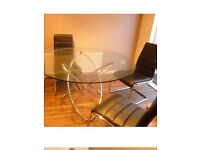 REDUCED... Dining table and four chairs.. glass top / black and chrome chairs
