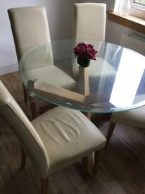 Round glass oak dining table and 4 cream leather chairs