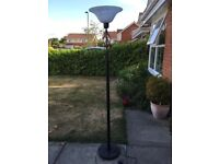 Tall ornate black metal and glass shade lamp