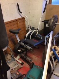 Gym equipment, stack machine, weight benches and free weights, exercise bike and punch bag.