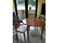 Dining table with drop leaf sides and 4 chairs.