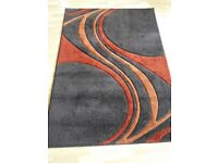 Good quality thick dark brown rug with terracotta swirls for sale
