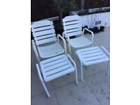 Two metal patio chairs with footstools