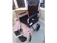 Lightweight, folding, pink wheelchair with handbrake..
