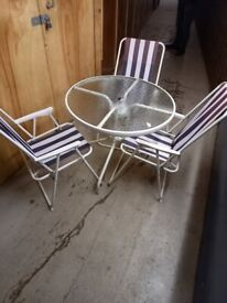 metal framed glass topped patio table with 3 chairs