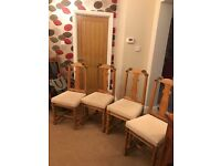 4 oak dining chairs with cream upholstered seats.