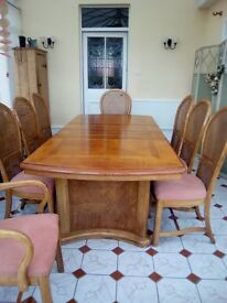 Beautiful solid wood 8 place dinning table with 2 carver and 6 wood and weave back chairs.