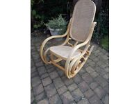 A WOODEN ROCKING CHAIR RATTEN BACK AND SEAT