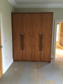 Bespoke wood veneer 4 door wardrobe with leather handles and lighting.