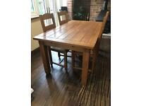 Solid oak extendable dining room table and 4 chairs.
