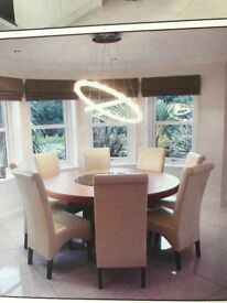 Very large round walnut dining table with 8 cream leather chairs