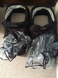 Two carry cots and rain covers for mountain buggy duet