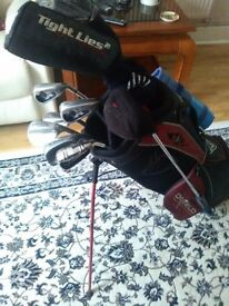 A set of mixed golf clubs ready to play including a stand bag.