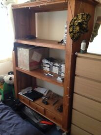 Wooden balinese shelving unit with 3 small drawers.