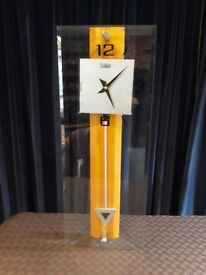 Wall clock - modern, glass fronted, battery operated. With pendulum.