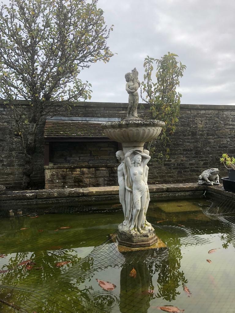 Stone statue with bird bath