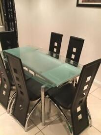 Extending glass table black leather chairs