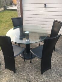 Round glass dining table with 4 black leather chairs.