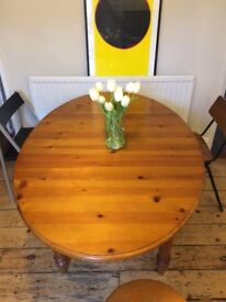 Extendable oval pine dining table with two chairs