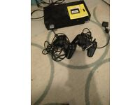 SOny PS2 console with games, control pads and memory cards.