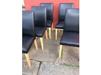 Black leather chairs with wooden legs