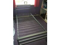 Single metal frame bed with mattress and duvet