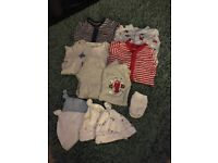 Bundle of new born sleeping suits and hats and mittens