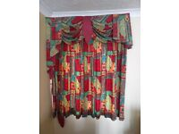 Multi colored patterned tie back curtain with a pelmet, dressed with swags and tails finish