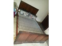 Double bed base with carved wooden head and foot boards.