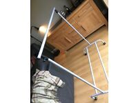 Adjustable, metal hanging rail for clothes. On wheels so easy to move around.
