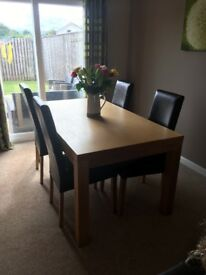 Solid oak dining table with 4 brown leather chairs