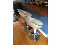 Modernist and stylish white and chrome bar stools with adjustable height