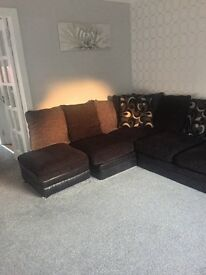 Black corner sofa with scatter cushions and footrest