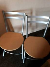 2 metal folding chairs with wooden seats