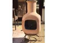 Clay chiminea and plastic garden seat with storage for the wood