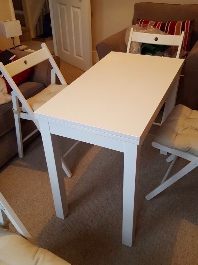 Small white extendable Ikea Bjursta dining table and 4 white Ikea