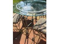 Round glass top dining table and 4 chairs with ornate metal base.