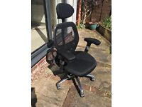Black office chair with headrest, mesh back, fully adjustable. On casters.