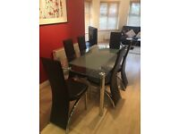 Glass dining table with 6 chocolate brown leather and metal dining chairs - excellent condition