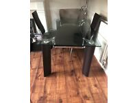 Modern dining table with four chairs for sale.