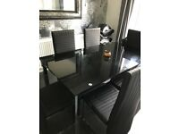 Show home Black Glass dining table with 6 chairs. Dinner table looking for quick sale.