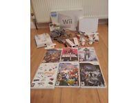 Wii Console, all leads, sensor bar, 7 games, charging unit, 2 x controllers/nunchuks, 1x gun cradle