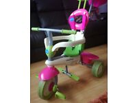 pink and green childs trike with sun visor for age range 6-36 months. Good condition.