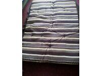 Cushion for a swinging hammock