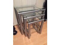 Modern set of 3 steel, chrome and clear glass nested tables.